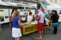 Besucher des Afrikafests am Infostand der Amnesty-Gruppe Ingolstadt.